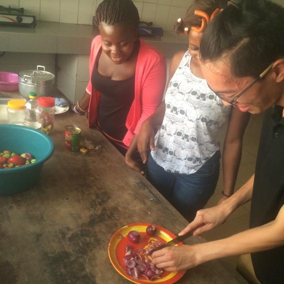 Kengo cutting onions for Jollof rice